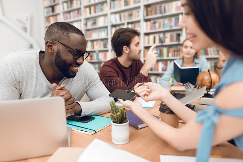 Group of ethnic multicultural students in library. Asian girl showing phone to black guy. stock photography