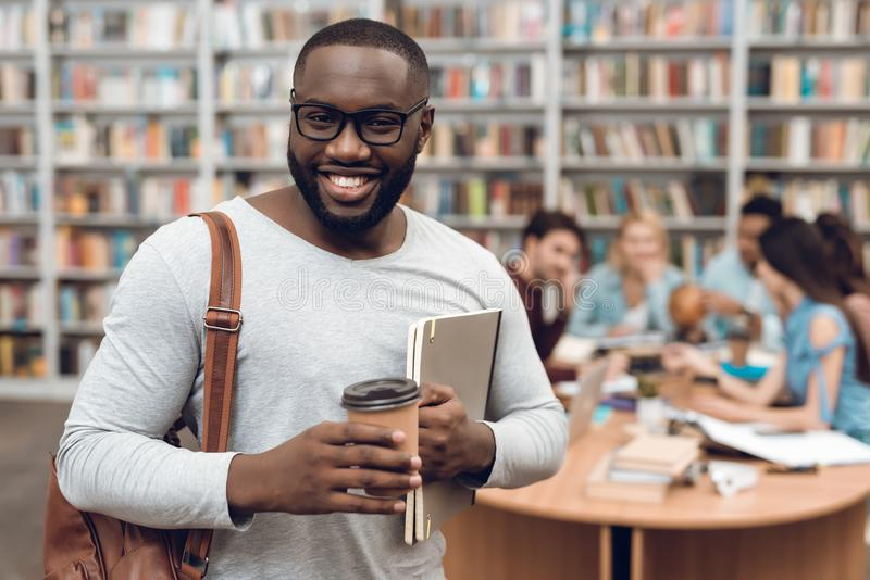 Group of ethnic multicultural students in library. Black guy with notes and coffee. royalty free stock photography