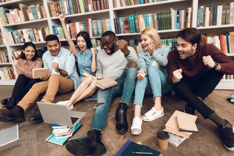 Group of ethnic multicultural students in library watching sports on laptop. stock photography