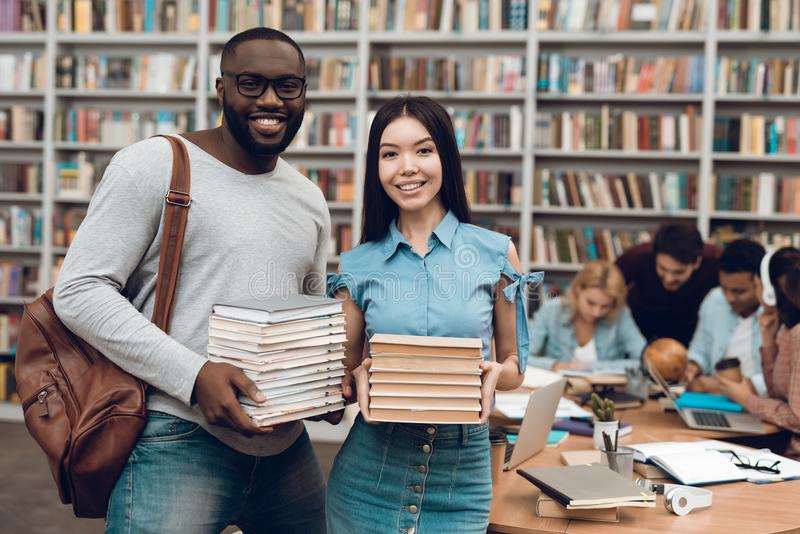 Group of ethnic multicultural students in library. Black guy and asial girl with books. stock image