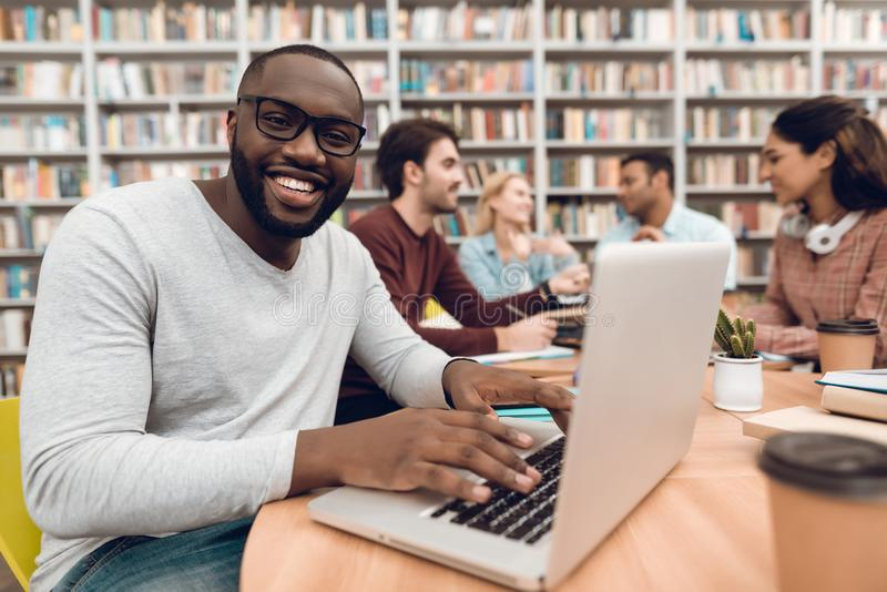 Group of ethnic multicultural students in library. Black guy on laptop. royalty free stock images