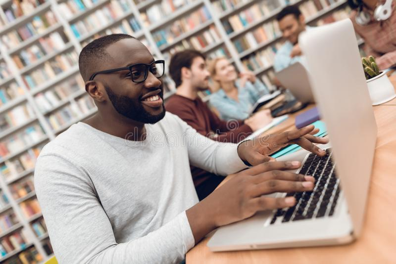 Group of ethnic multicultural students in library. Black guy on laptop. stock images