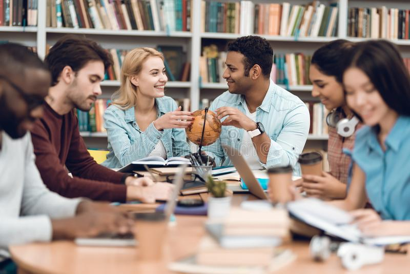 Group of ethnic multicultural students in library. Students are talking and reading. stock photos