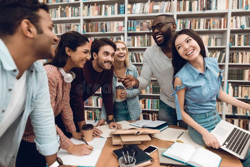Group of ethnic multicultural students talking and laughing in library. stock images
