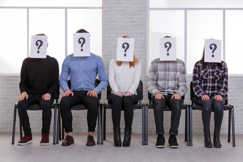 A group of guys and girls, sitting on chairs, hands on their knees and on their faces is a question mark. A group of European guys and girls, sitting on chairs royalty free stock photos