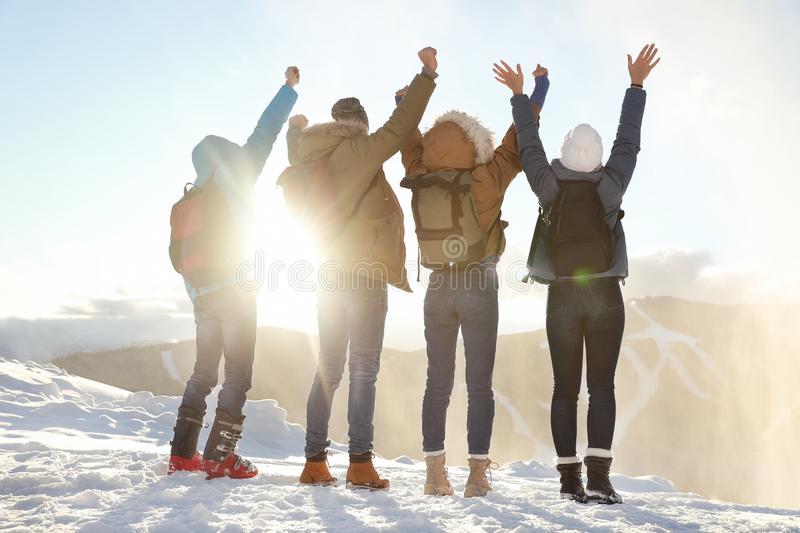 Group of excited friends with backpacks enjoying mountain stock photo
