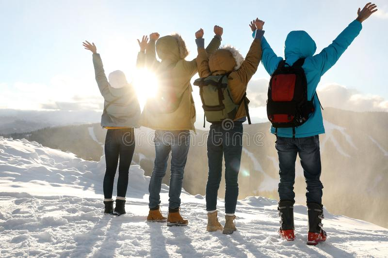 Group of excited friends with backpacks enjoying view during winter vacation royalty free stock images