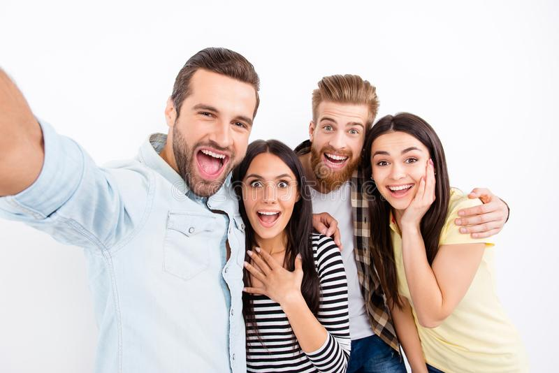 Group of excited friends making selfie on the camera of smartphone showing great emotions of amazement and excitement on white ba stock photography