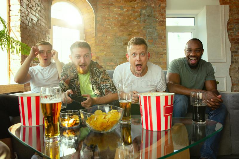 Group of excited friends playing video games at home royalty free stock photography