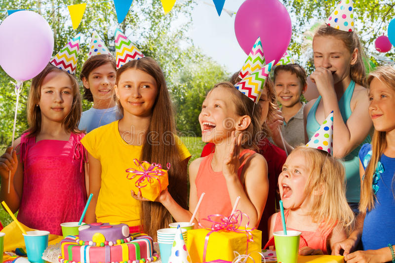 Group of excited kids congratulating birthday girl royalty free stock photo