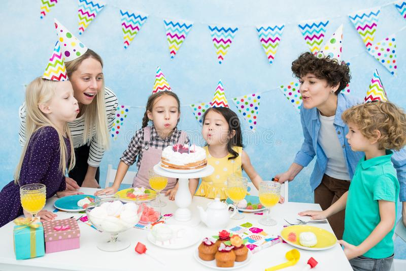 Kids blowing out candles at birthday party royalty free stock photos