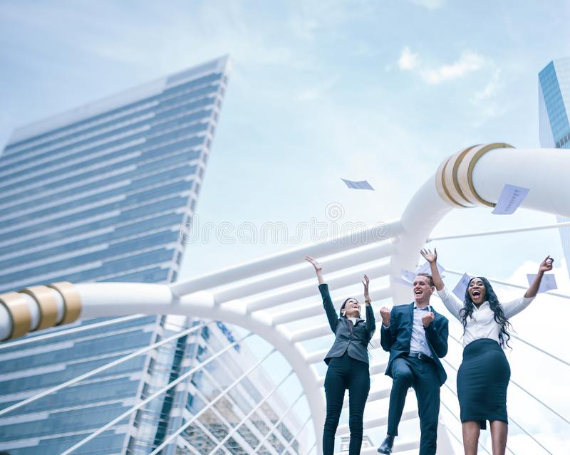 Group of excited multi racial business people throwing papers in city. stock images