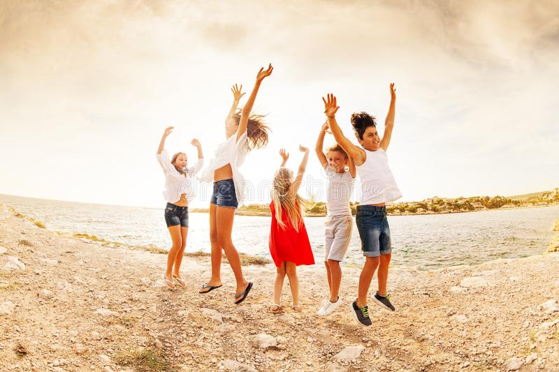 Excited teens jumping and having fun on the beach stock image