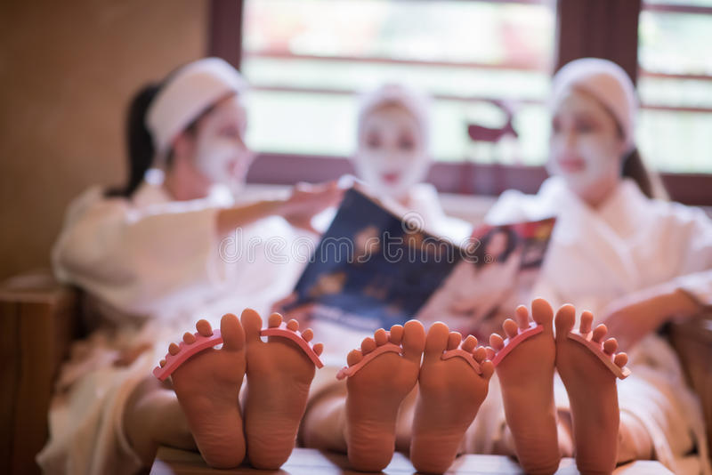 Group of famale friends in spa. Have fun, celebrate bachelorette party with face mask stock photo
