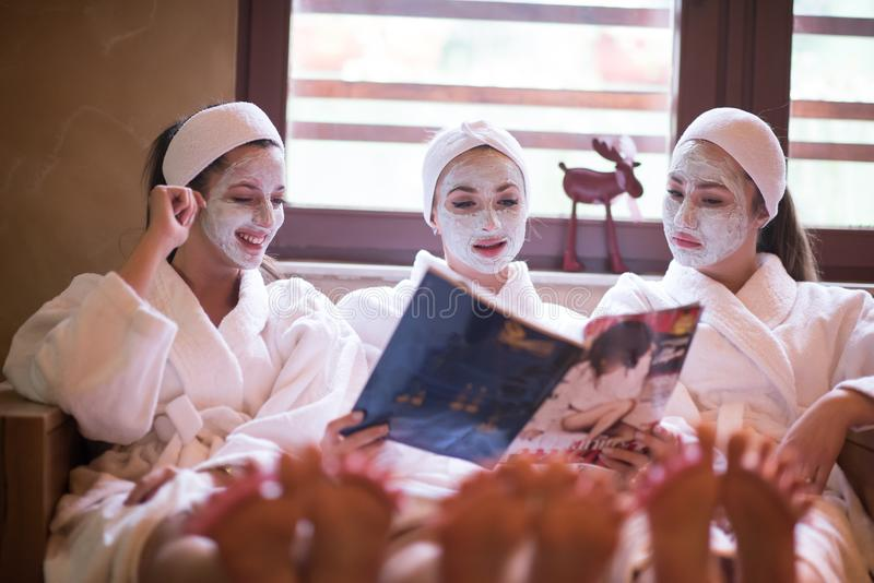 Group of famale friends in spa. Have fun, celebrate bachelorette party with face mask stock image