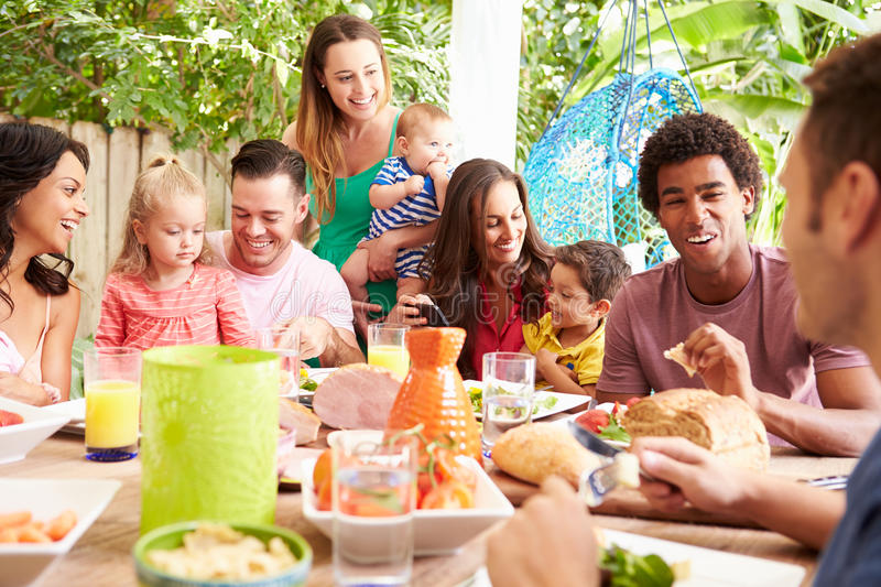 Group Of Families Enjoying Outdoor Meal At Home royalty free stock photography