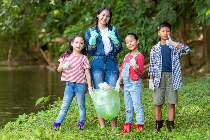 Group family asian children collecting garbage and plastic on the river to dumped into the trash for volunteer charity save enviro royalty free stock photos