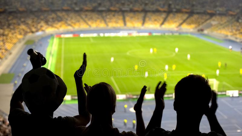 Group of fans cheering for football team victory at crowded stadium, competition stock photo