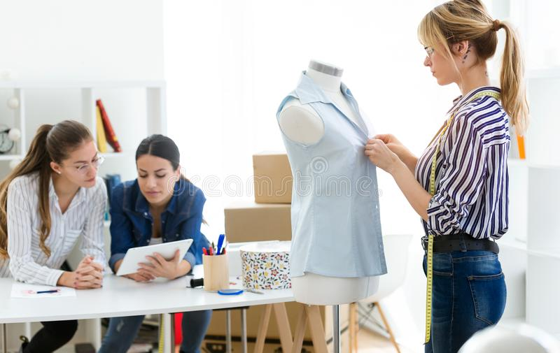 Group of fashion designers working and deciding details of new collection of clothes in the sewing workshop royalty free stock photography