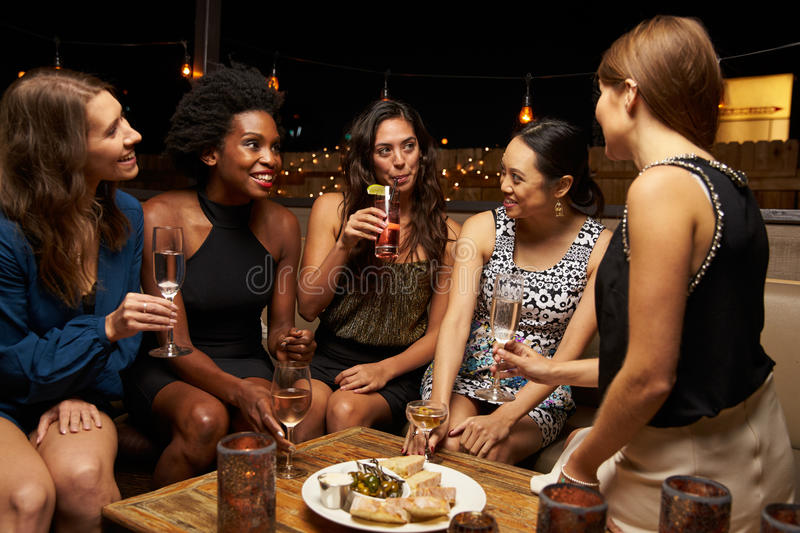 Group Of Female Friends Enjoying Night Out At Rooftop Bar stock photos