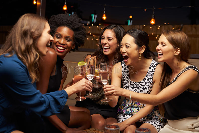 Group Of Female Friends Enjoying Night Out At Rooftop Bar royalty free stock images