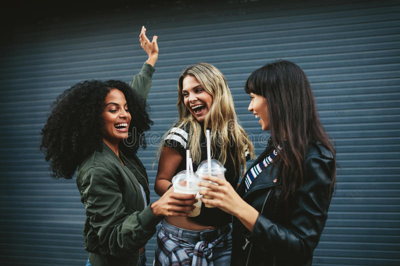 Group of female friends having fun with ice coffee stock images