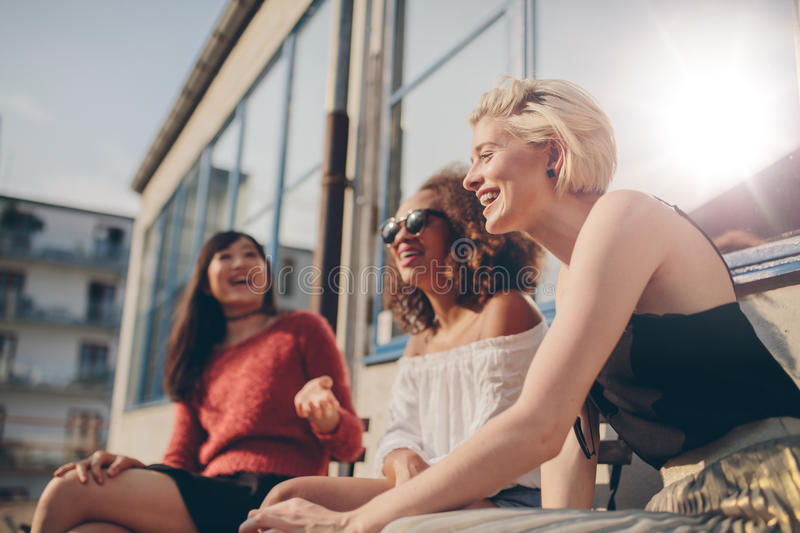 Group of female friends having fun outdoors. Group of female friends having fun while sitting at outdoor cafe. Three young women sitting in a terrace chatting stock photography