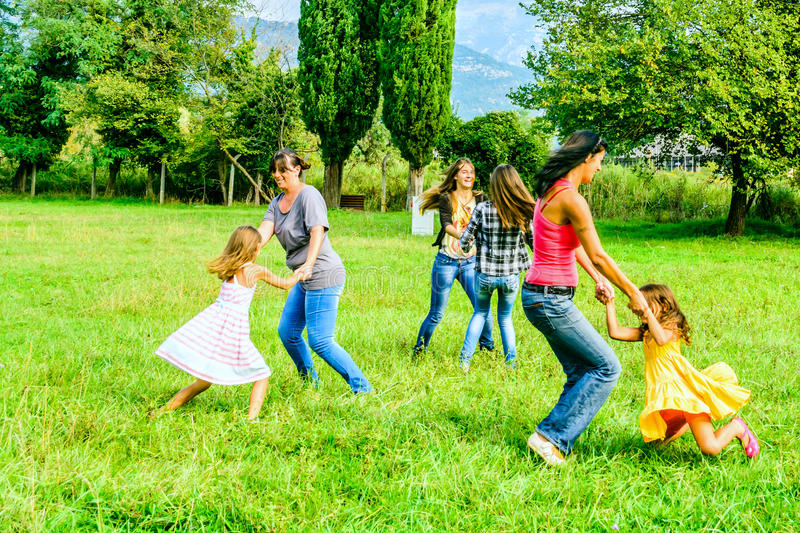 Group of female friends holding hands and playing in the park stock photo