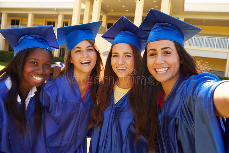 Group Of Female High School Students Celebrating Graduation. Wearing Blue Cape And Mortar stock image