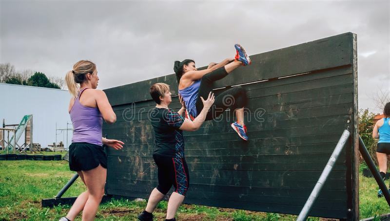 Female participants in obstacle course climbing wall. Group of female participants in an obstacle course climbing a wall royalty free stock photo