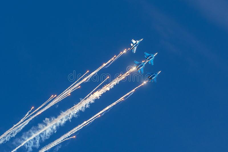 Group of fighters in the blue sky with a trace of black smoke and heat guns, bright flashes weapon shots.  stock image
