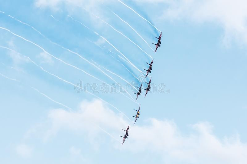Group of fighters in the blue sky with a trace of black smoke and traces of white vapor vortex clouds stock images