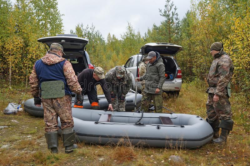 Group of fishermen prepares inflatable boats for fishing stock photos