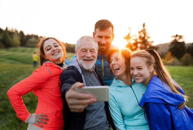 A group of fit and active people resting after doing exercise in nature, taking selfie. stock image