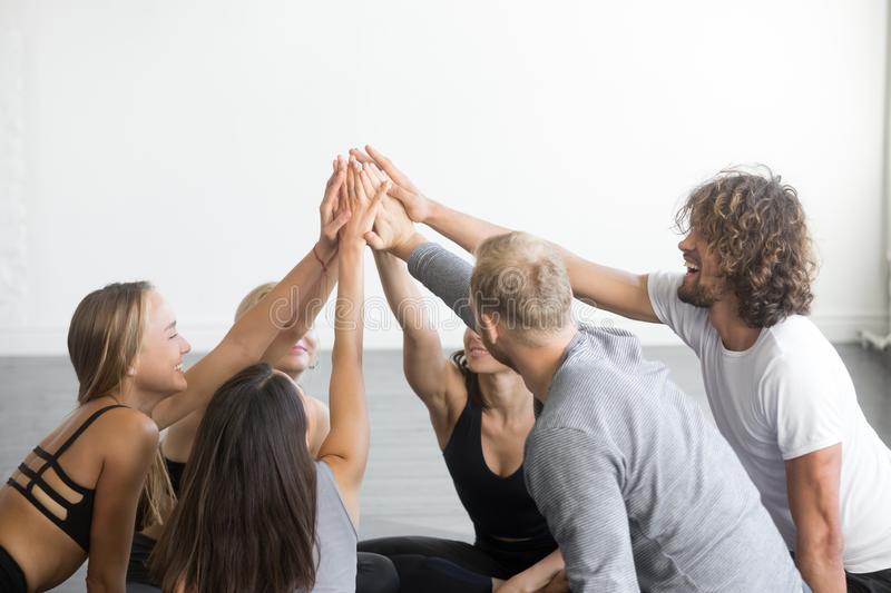 Group of fit happy people giving high five royalty free stock photo