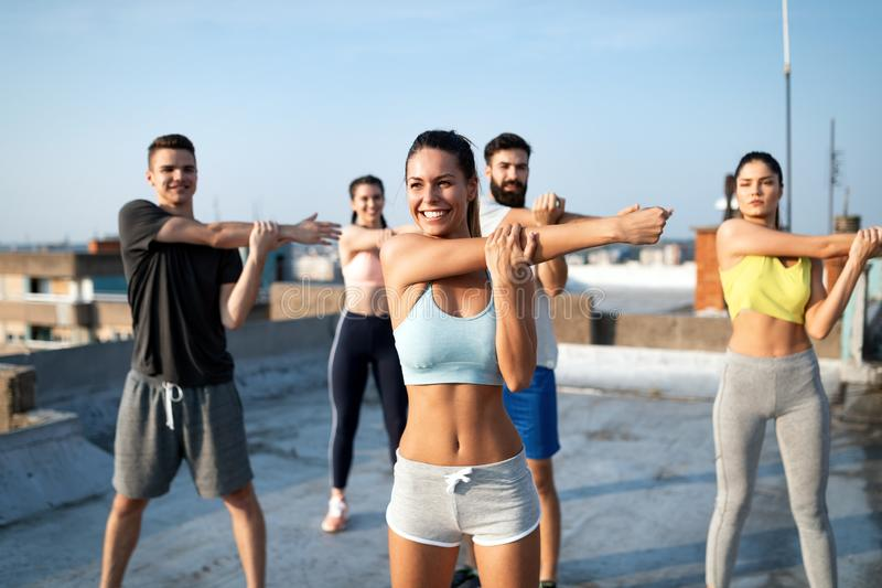 Group of happy fit friends exercising outdoor in city royalty free stock photo