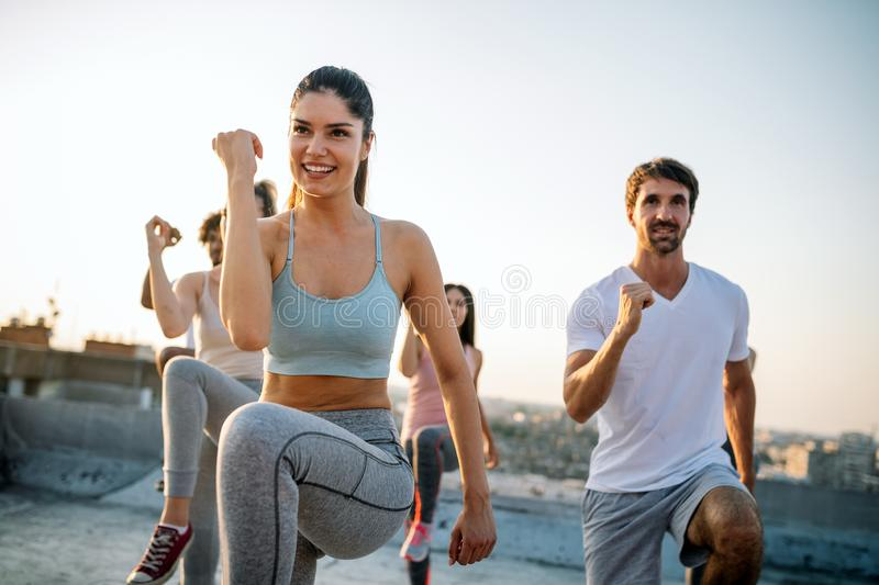 Group of happy fit friends exercising outdoor in city stock image