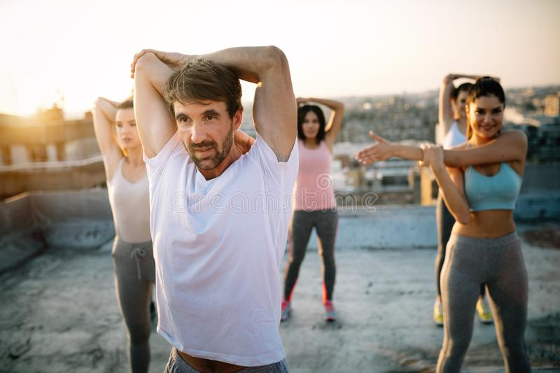 Group of happy fit friends exercising outdoor in city royalty free stock photography