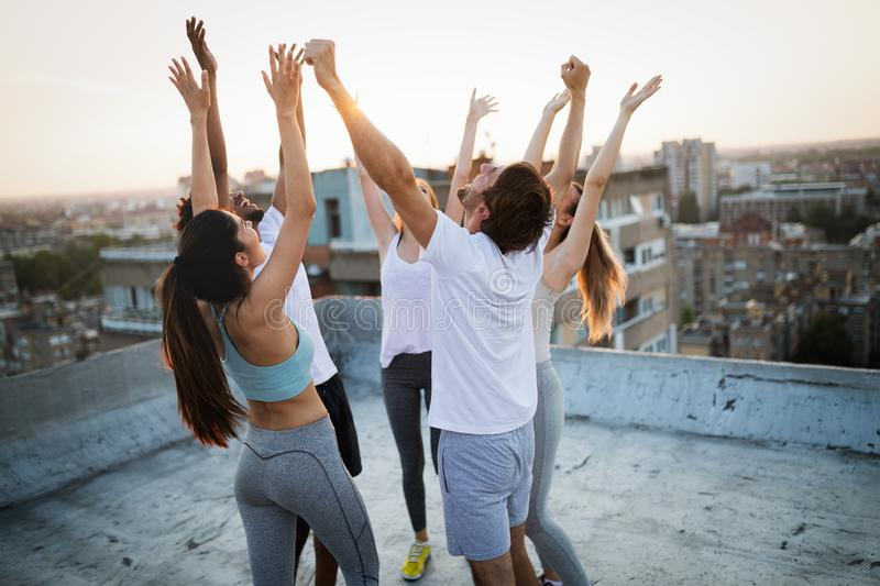 Group of happy fit friends exercising outdoor in city. Group of fit happy people training outdoor on the roof royalty free stock images