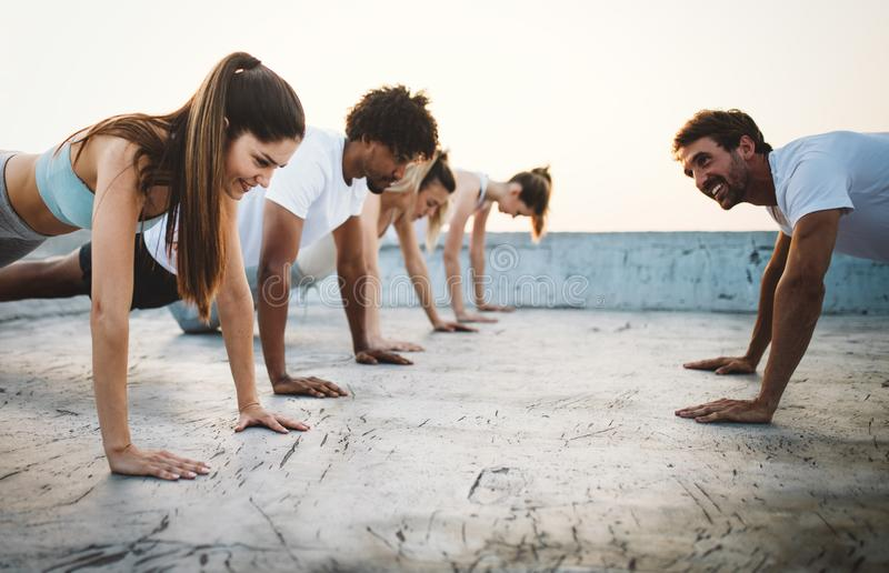 Group of happy fit friends exercising outdoor in city. Group of fit happy people training outdoor on the roof stock images