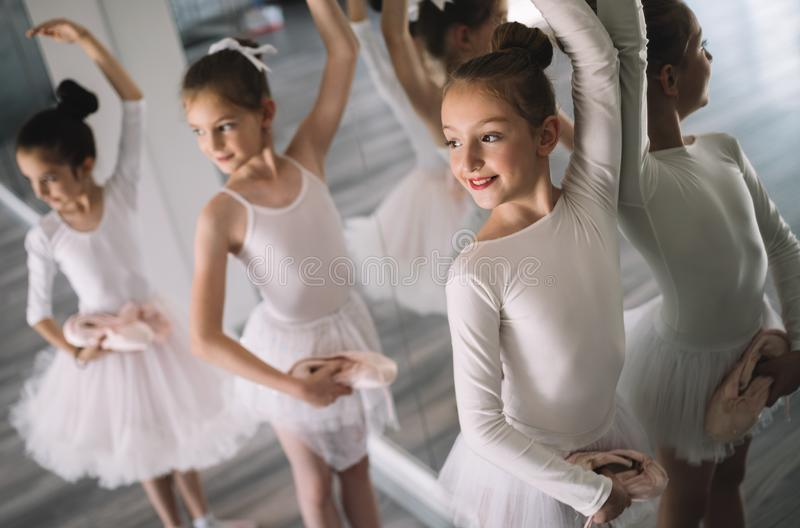 Group of little ballerinas girls doing exercises in dance school. Group of fit little ballerinas doing exercises in dance school stock photography