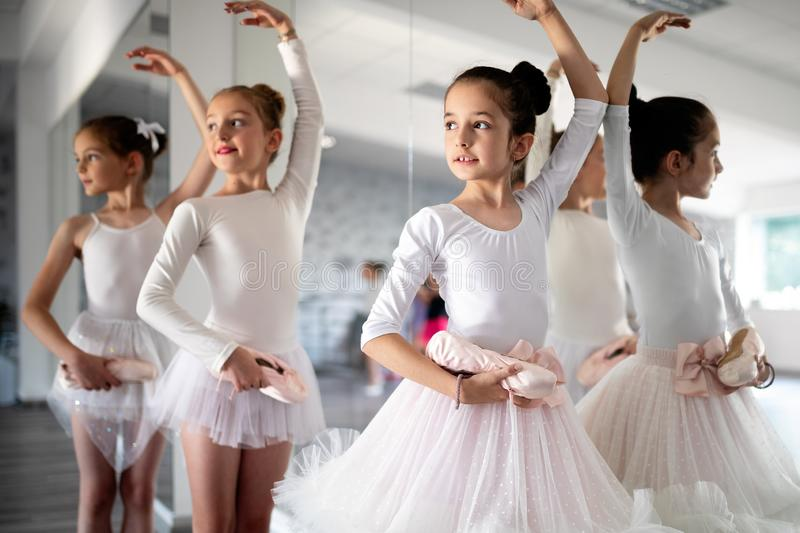 Group of little ballerinas girls doing exercises in dance school. Group of fit little ballerinas doing exercises in dance school stock image