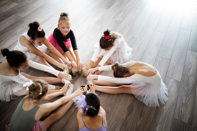 Group of little ballerinas girls doing exercises in dance school. Group of fit little ballerinas doing exercises in dance school royalty free stock photo