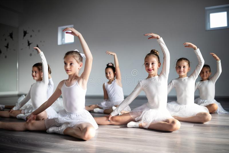 Group of little ballerinas girls doing exercises in dance school. Group of fit little ballerinas doing exercises in dance school royalty free stock image