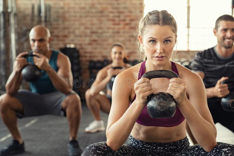 Fitness woman squatting with kettle bell. Group of fit people holding kettle bell during squatting exercise at crossfit gym. Fitness girl and men lifting stock images