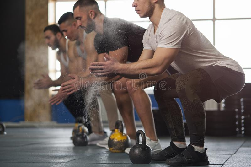 Group of Fit Young Men Preparing for Kettlebell Training. Sporty Male Adults During Workout SessionStrength Training, Powerlifting and Sports royalty free stock photo