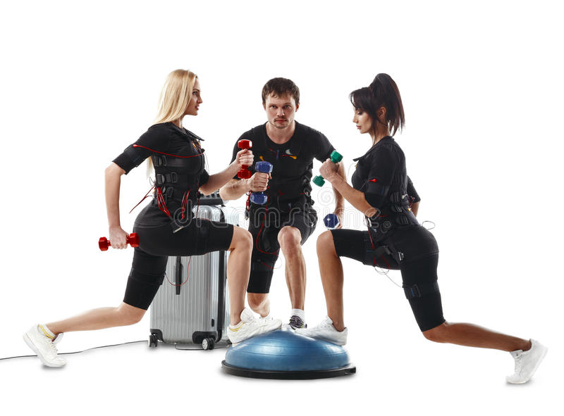Group of fitness athletes in EMS suits doing lunge exercise with dumbbells stock photo