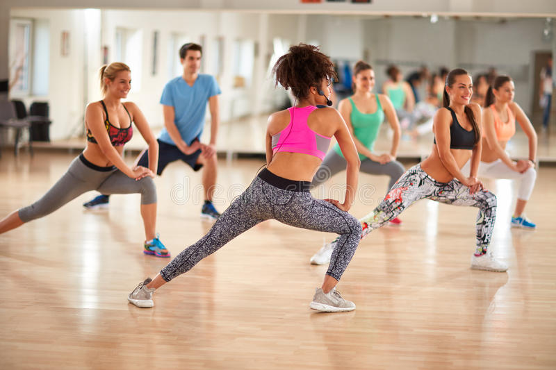 Group of fitness exercisers in colorful sports clothes in fitness class. Young group of fitness exercisers in colorful sport clothes with female instructor in royalty free stock photo