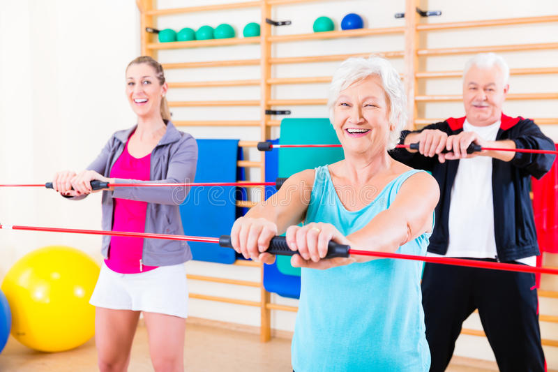 Group at fitness training with gymnastic bar stock photo