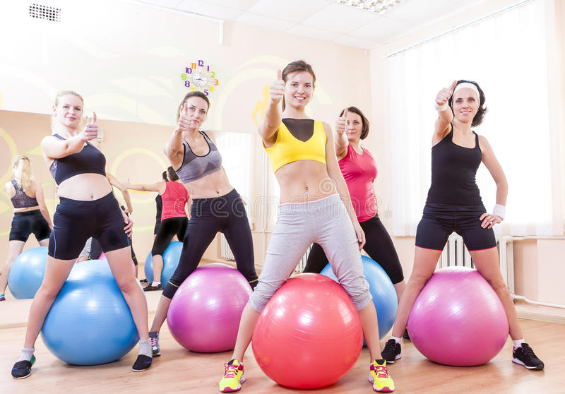 Group of Five Caucasian Female Athletes Having Exercises With Fitballs in Gym and Showing Thumbs Up Sign. royalty free stock photo